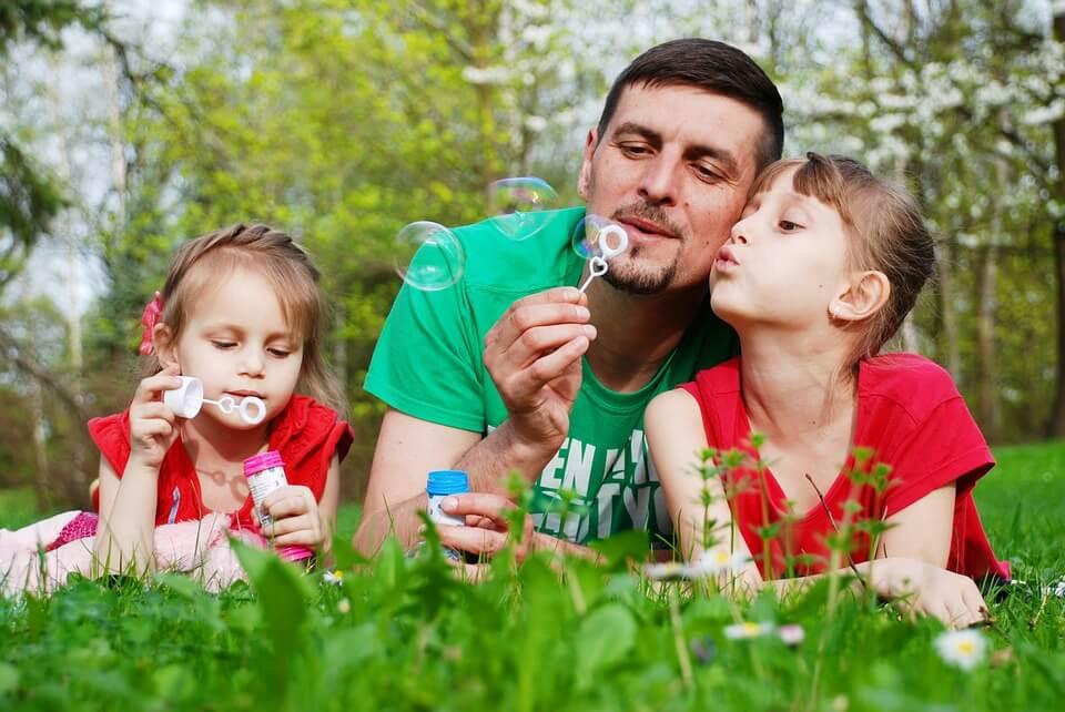 На фото изображено как папа пускает мыльные пузыри с дочками.