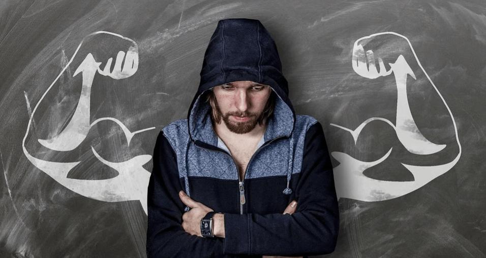 На фото изображен слабый человек, за спиной которого нарисованы мускулистые руки.