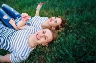 Парень и девушка на траве. Где найти красивые цитаты про любовь под фото.
